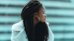 Profile of an adorable young black female with big dreadlocks, round earrings, and piercing in her nose, she is looking aside while standing outdoors with a striped facade in defocused background