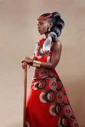 Profile of an attractive young African woman with long hair wearing traditional clothing holding a staff while standing against a brown background