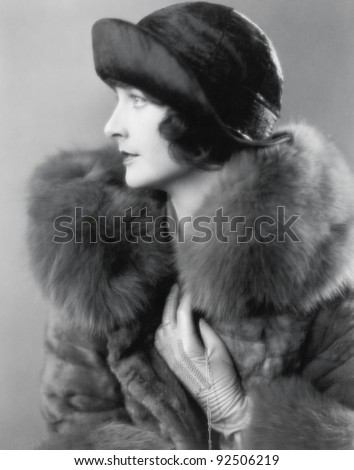 Profile of an elegant woman in a fur coat and satin hat