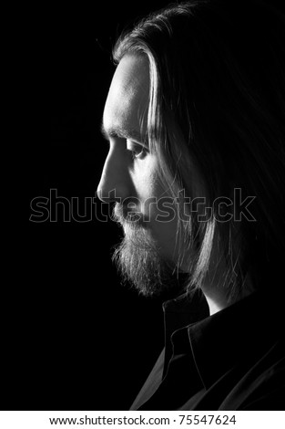 profile of bearded man looking down, low key