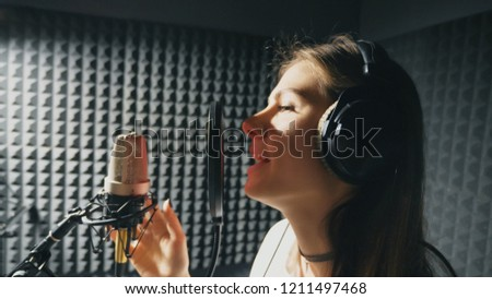Profile of beautiful girl singing in sound studio. Young female singer emotionally recording new song. Woman sings to microphone. Working of creative musician. Show business concept. Slow motion. #1211497468