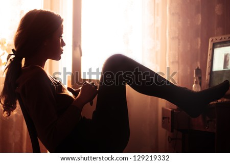 Profile of beautiful girl sitting in the room in the morning