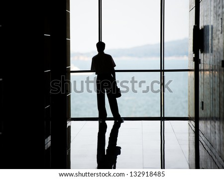 Profile of business people against the windows in an office tower.