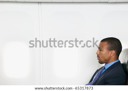 Profile of businessman on airplane - stock photo