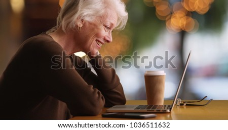 Profile of cheerful Caucasian woman in her 50s video chatting on laptop outside