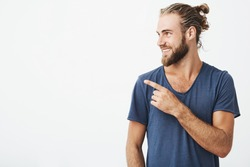 Profile of cheerful handsome man with fashionable hairstyle and beard smiling brightfully and pointing at free space for advertisement.