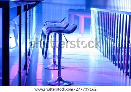 Profile of Empty Bar Stools Along Bar Illuminated in Purple Light at Night Club
