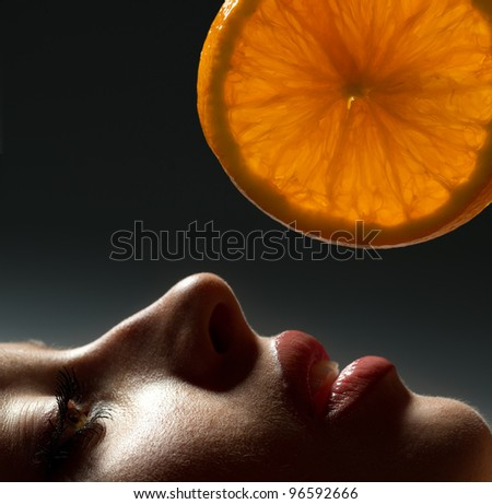 Profile of female face with orange slice over dark background