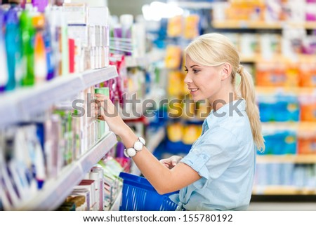 Profile of girl at the shop choosing cosmetics among the great variety of products. Concept of consumerism, retail and purchase