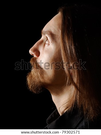 profile of handsome man looking up, on black background - stock photo