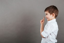 Profile of happy little boy in white shirt standing and pointing up over grey background