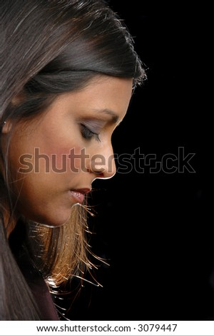 Profile of indian girl looking down against a black background - stock ...