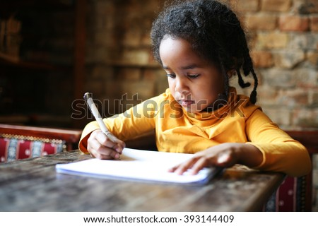 Profile of little African girl writing  at home.