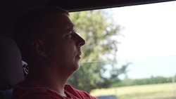 Profile of lorry driver operating the truck through countryside. Adult trucker driving a car at country road. Man riding to destination. Logistics and transportation concept. Close up Slow motion.