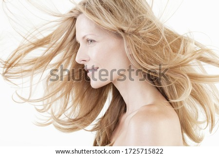 Profile of mid adult woman with windswept hair against white background