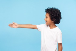 Profile of polite cheerful preschool boy with curly hair in white T-shirt giving hand to handshake, gullible trusting child meeting with friendly smile. indoor studio shot isolated on blue background
