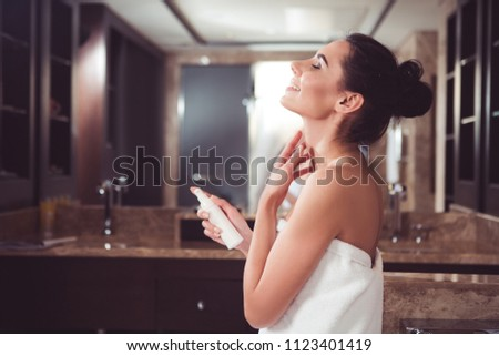 Profile of satisfied woman applying cream on neck with joy. She is holding cosmetic container in one hand while gently touching skin with another. Copy space in left side #1123401419