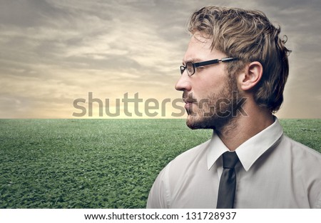 profile of serious young man with the country behind