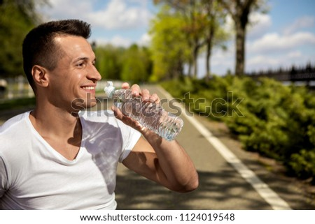 Profile of smiling guy drinking water from bottle. He is spending sunny day in green park. Enjoying warm weather walking outside concept