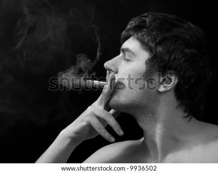 Profile of smoking man on black background, black-and-white