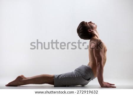 Profile of sporty muscular young man working out, yoga, pilates, fitness training, exercises for flexible spine, urdhva mukha shvanasana, upward facing dog pose, gray background, low key shot