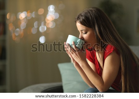 Profile of woman drinking coffee sitting on a couch in the night at home