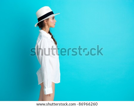 profile of young woman standing on blue background, with white hat and man's shirt, copy space