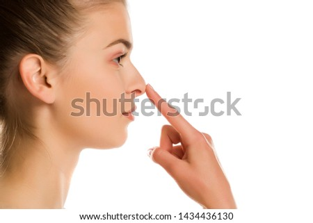 profile of young woman touches her nose on white background #1434436130