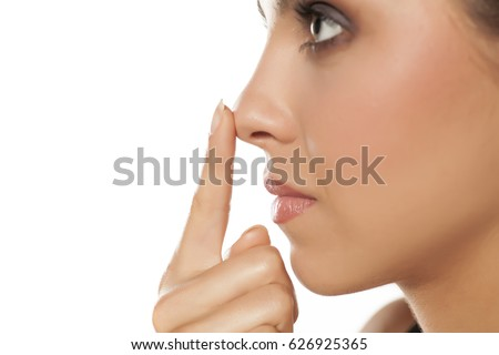 Profile of young woman touching her nose #626925365