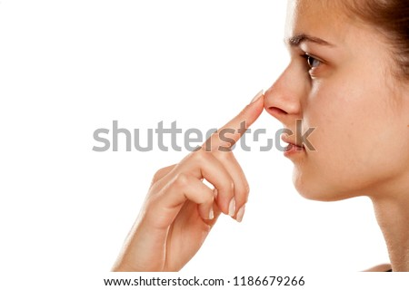 Profile of young woman touching her nose on white background