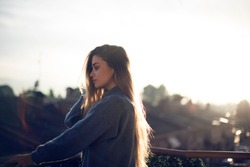 Profile or side view of beautiful charming blonde girl looking away, standing outdoors in a balcony during sunset has thinking expression. Lovely blonde girl wearing casual clothes. Backlighting
