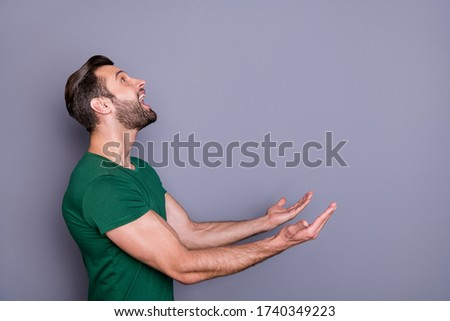 Profile photo of attractive amazed handsome guy good mood raise arms up side empty space waiting novelty product falling catch wear casual green t-shirt isolated grey color background Сток-фото ©