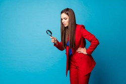Profile photo of attractive business lady holding enlarge loupe searching piece of evidence wear luxury trend red suit blazer pants blouse shirt isolated blue color background