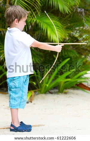 Profile photo of cute boy playing with wooden bow and arrows