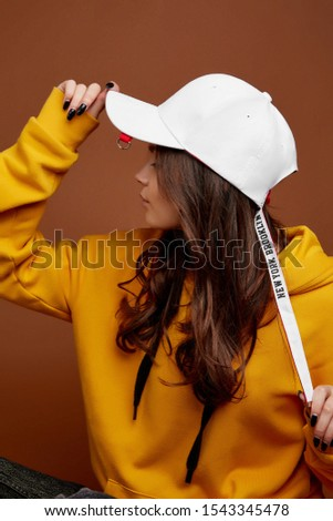 Profile photo of European lady with long brown hair in a black baseball cap with ring on the visor and long white and red bands. The girl with black nails is wearing a yellow hoodie.