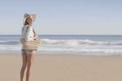 profile photo of happy fashion blonde girl smiling in the beach, wearing hat, a bag, shorts and white shirt, in the beach, with defocused background,