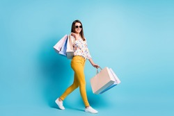 Profile photo of lovely young girl walk carry store bags wear sunglass geometry print shirt yellow trousers isolated blue color background