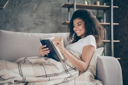 Profile photo of pretty amazing dark skin wavy lady hold book reading favorite love story historic novel lying comfy couch covered with plaid blanket living room indoors