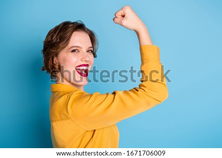 Profile photo of pretty cheerful lady hold raise biceps hand arm show perfect biceps gym training strong powerful woman wear yellow shirt isolated bright blue color background Stock foto ©