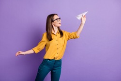 Profile photo of pretty girl hold throwing origami plane wear eyewear yellow shirt blue trousers isolated violet color background