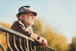 Profile photo of retired old white hair gloomy grandpa street central park walk look frustrated contemplating think past future lean metal fence wear autumn glasses jacket hat outside