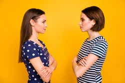 Profile photo of two amazing ladies standing opposite dislike each other competitive mood wear casual dotted and striped t-shirts isolated yellow background