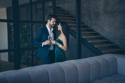 Profile photo of two classy stylish trendy people couple wealthy guy and lady standing close looking eyes drinking sparkling wine romance date wear fancy formalwear suit loft industrial indoors