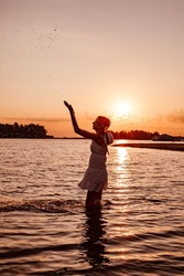 Profile photo of woman splashing water. Silhouette of a beautiful happy slender blonde in a summer dress and straw hat with ribbon on the background of the sunset and the beach with her hands raised.