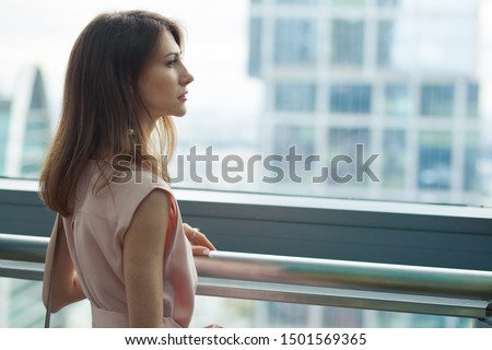 profile portrait of a beautiful slim young pensive serious brunette woman in a pink dress and with earrings near a huge window. Skyscrapers in the background