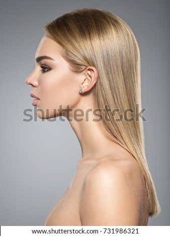 Profile portrait of  a beautiful young woman with long light straight  hair.   #731986321
