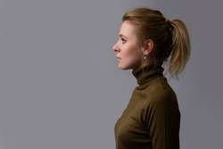 profile portrait of a casual pretty woman. Beautiful girl isolated on gray background