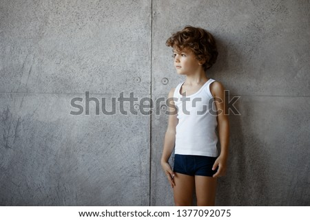 Profile portrait of a handsome little boy in underwear posing on concrete wall, looking a one side, copy space.