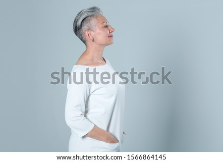 Profile portrait of a mature woman on a gray background.