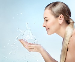 Profile portrait of a nice blond girl with pleasure washing her face in the morning by clear refreshing water, perfect clean skin, using anti acne remedy, hygiene concept